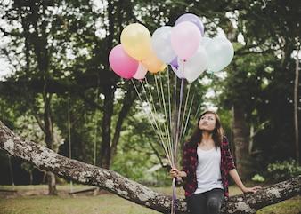 Mujer joven hipster sentado en rama de árbol con colores de globos en la mano, Relajante disfrutar de vacaciones.