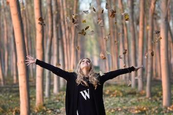 Mujer joven lanzando hojas al aire
