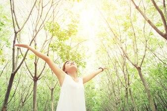 Mujer joven mirando al cielo con los árboles de fondo