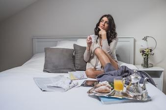 Mujer joven pensativa con taza de café en la mano