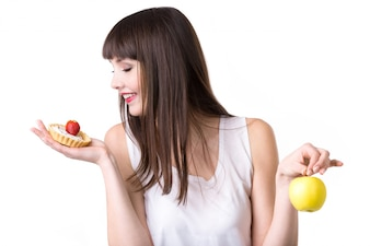 Mujer joven que elige la torta en vez de la manzana