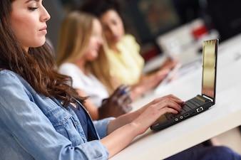 Mujer joven que estudia con la computadora portátil en el escritorio blanco.