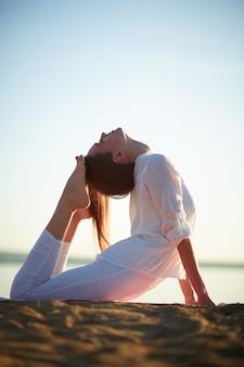 Mujer joven que hace ejercicio de yoga al aire libre