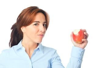 Mujer joven que muestra una manzana roja mordida