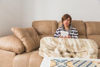 Mujer joven relajada usando su tableta en el sofá