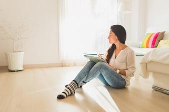 Mujer joven sentada en el suelo y mirando hacia un lado