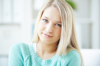 Mujer joven sonriente con suéter verde