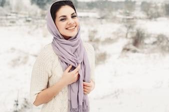 Mujer joven sonriente cubriéndose la cabeza y el cuello