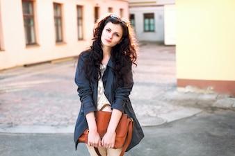 Mujer joven sonriente sujetando su bolso