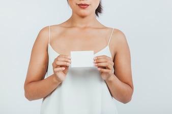 Mujer joven sosteniendo una tarjeta de visita con ambas manos