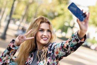 Mujer joven tomándose una autofoto y mostrando el gesto de la victoria
