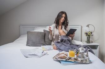 Mujer joven usando la tableta mientras desayuna