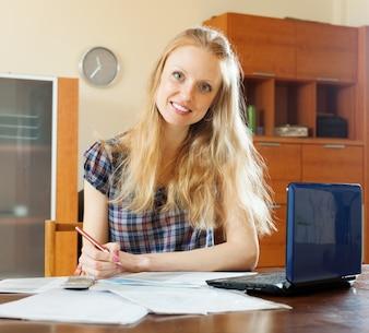 Mujer leyendo el documento financiero en la mesa
