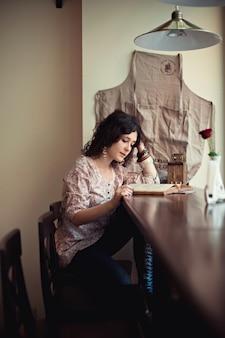 Mujer leyendo sobre una mesa de madera