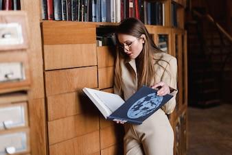Mujer leyendo un libro de pie