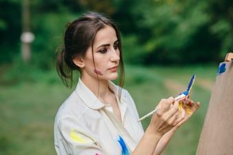 Mujer llenando su pincel de pintura azul