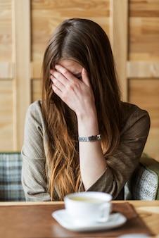 Mujer llorando y cubriéndose la cara con la mano