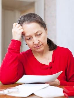 Mujer madura tristeza con las facturas