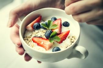 Mujer manos sosteniendo el tazón de fuente con muesli sabroso con las frutas, la avena y el yogur. De cerca. Concepto De Alimentos Saludables.