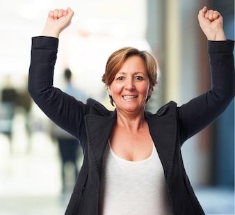Mujer mayor celebrando con los brazos en alto
