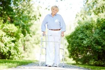 Mujer mayor con el caminante en el parque