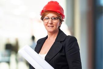 Mujer mayor con planos y casco