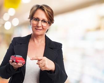 Mujer mayor con un coche rojo