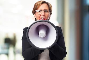 Mujer mayor de negocios hablando por un megáfono