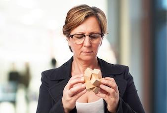 Mujer mayor de negocios mirando un juego de inteligencia de madera