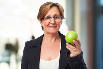 Mujer mayor de negocios sujetando una manzana