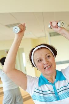Mujer mayor ejercitándose con pesas