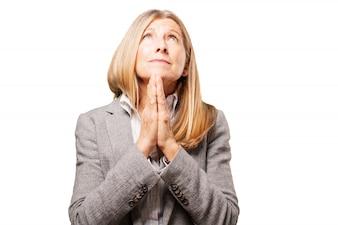 Mujer mayor elegante rezando