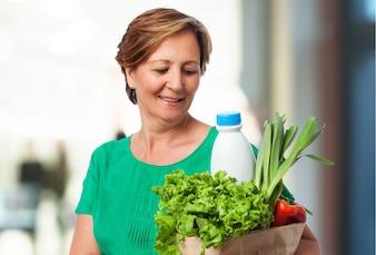 Mujer mayor feliz con la cesta de la compra