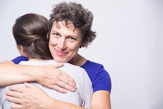 Mujer mayor feliz que abraza a la hija adulta joven