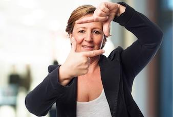Mujer mayor haciendo el gesto de un marco