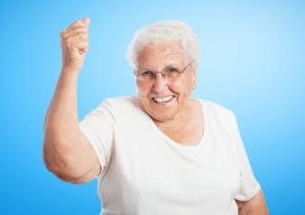 Mujer mayor sonriendo con un puño en alto