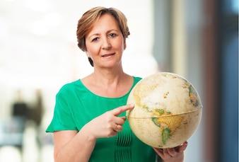 Mujer mayor sujetando un globo del mundo