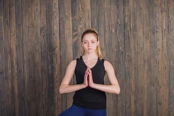Mujer meditando sobre fondo de madera