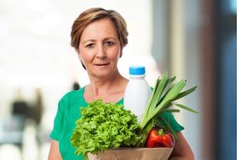 Mujer mirando bol con verduras y leche
