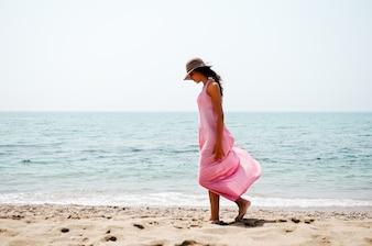 Mujer mirando la arena de la playa mientras camina