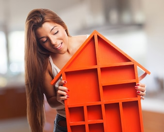 Mujer mirando una casa de juguete naranja