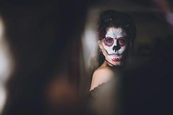 Mujer mirándose al espejo con la cara vestida para el carnaval