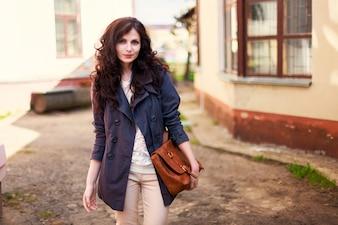 Mujer morena con el pelo rizado sujetando su bolso