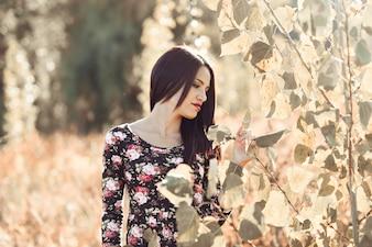Mujer morena tocando algunas hojas en el campo