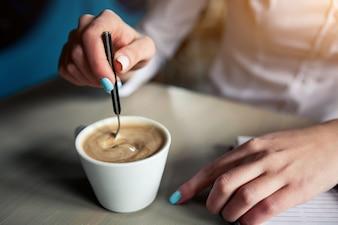 Mujer moviendo el café con una cucharilla