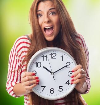 Mujer nerviosa que sostiene el reloj de pared en las manos.