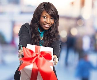 Mujer ofreciendo un regalo blanco con un lazo rojo