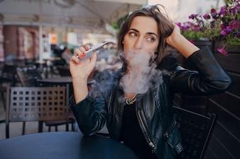 Mujer pensando con un cigarro electrónico en la mano