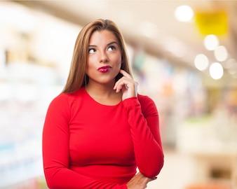 Mujer pensativa con los labios pintados de rojo