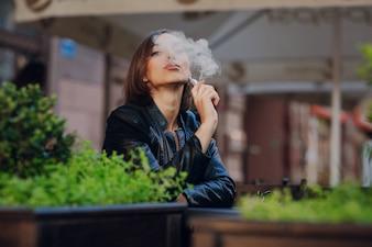 Mujer pensativa fumando en la calle